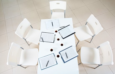 Above view of table with papers and cups of coffee surrounded by several chairs  photo