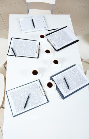 Above view of table with papers and cups of coffee during break  photo
