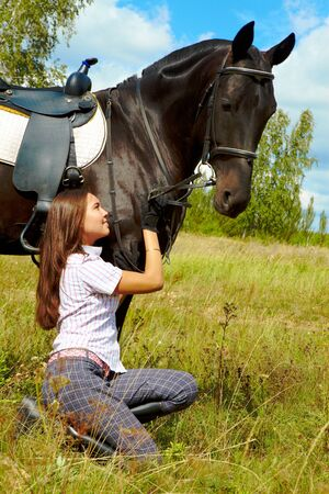Image of happy female taking care of purebred horse outdoors photo