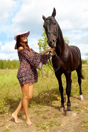 Image of smart female in hat and dress taking care of purebred horse outdoors