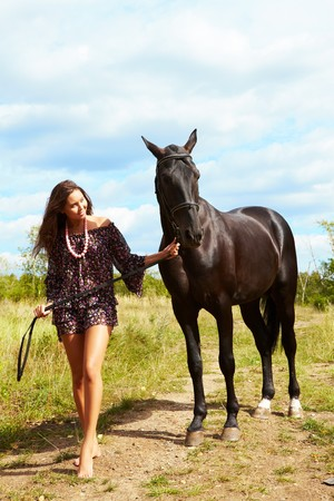 thoroughbred: Image of barefoot female walking down path with purebred horse outdoors