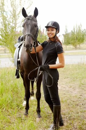equitation: Image of happy female jockey with purebred horse outdoors