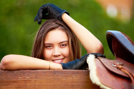 gloved: Image of happy female holding saddle and looking at camera