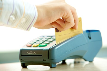 business transaction: Close-up of human hand putting credit card into payment machine in shopping center
