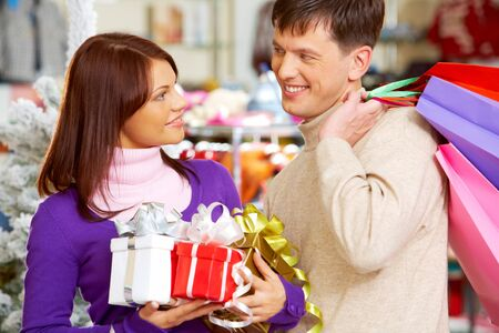 Photo of handsome man looking at his wife during shopping in trade center photo