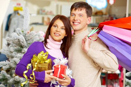 Image of attractive couple looking aside and smiling in trade center photo