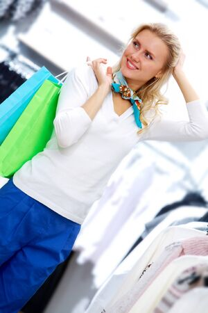 Portrait of pretty woman with bags in clothing department photo