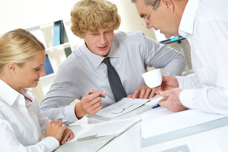Portrait of three businesspeople discussing plan at meeting Stock Photo - 7695763