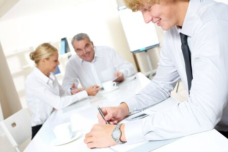 Portrait of confident businessman thinking over business plan with communicating partners at background Stock Photo - 7695750