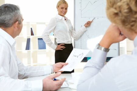 Photo of successful employee standing by whiteboard while her colleagues listening to her photo