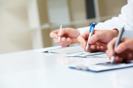 Image of row of human hands writing on papers at seminar Stock Photo - 7695709
