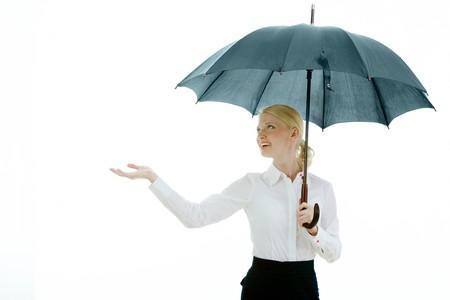 Happy businesswoman under open umbrella stretching her arm photo