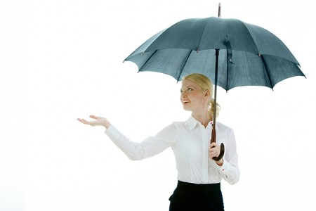 weather protection: Happy businesswoman under open umbrella stretching her arm