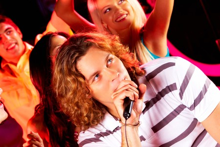 Photo of happy guy singing at party with company of friends dancing behind photo
