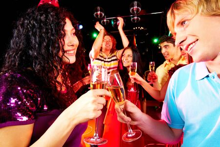 Portrait of happy couple toasting at party on background of joyful friends having fun photo