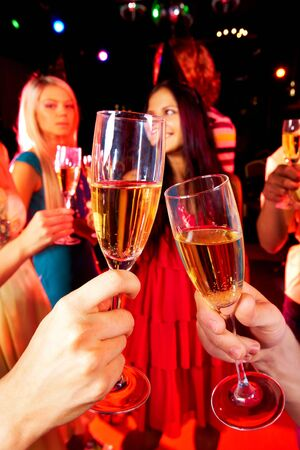 Image of toasting couple clinking glasses with champagne at party photo