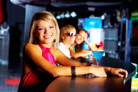 Image of row of smiling teens with pretty girl in front in the nightclub photo