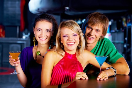 Portrait of young people with martini glasses laughing in the nightclub Stock Photo - 7695842