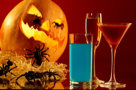 diabolic: Image of glasses with colorful drinks on background of Halloween pumpkin with spiders on it