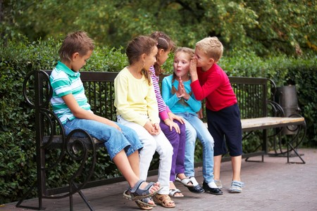 children talking: Portrait of happy friends resting on bench in park and chatting