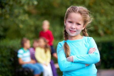 Portrait of happy girl crossing arms and looking at camera with her friends on background photo