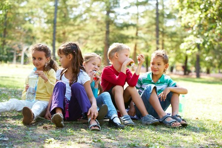 child food: Portrait of happy friends sitting on the ground in park and having meal time Stock Photo