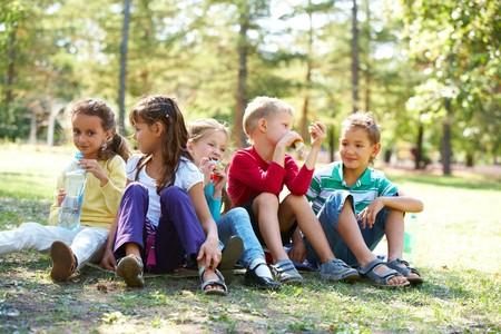 botanas: Retrato de amigos felices sentado sobre el terreno en el parque y tener tiempo de comida