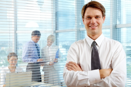 Business leader looking at camera with team of partners working in office behind photo