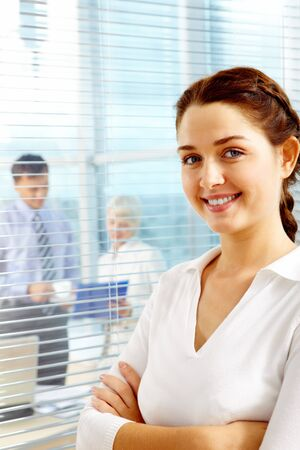 Female leader looking at camera on background of team of partners working in office photo