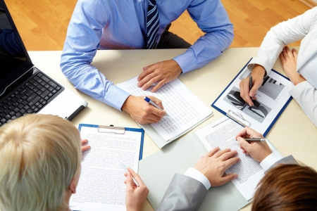 meeting place: Image of business people working with documents at meeting