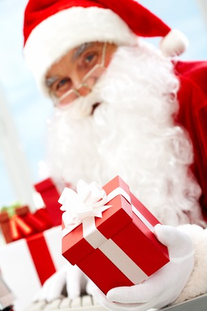 Photo of happy Santa Claus with red giftbox looking at camera Stock Photo - 7843921