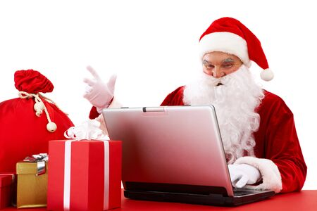 xmass: Portrait of Santa Claus in front of laptop with gifts near by