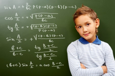 sums: Portrait of smart schoolchild by the blackboard with sums on it looking at camera
