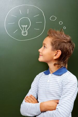 lad: Portrait of smart lad looking at blackboard with drawn lamp on it Stock Photo