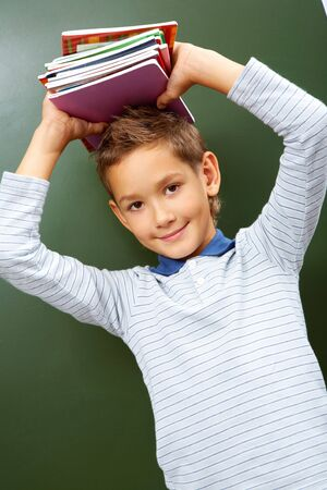 lad: Portrait of smart lad with copybooks on head looking at camera
