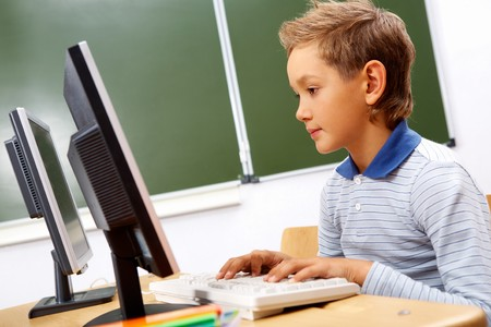 lad: Portrait of cute lad typing on computer board in classroom Stock Photo