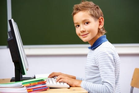 Portrait of cute lad typing on computer board and looking at camera in classroom Stock Photo - 7843951