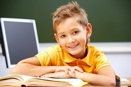 place to learn: Portrait of smart lad at his place looking at camera during reading lesson