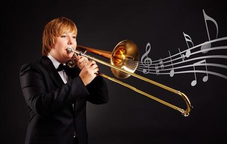 trombon: Retrato de joven mujer tocando el trombón en fondo negro