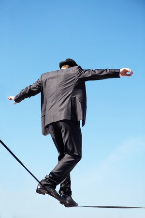hábil: Photo of skilled businessman walking down ribbon or rope against blue sky Banco de Imagens