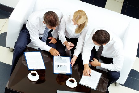 Image of company of successful partners discussing business plan at meeting photo
