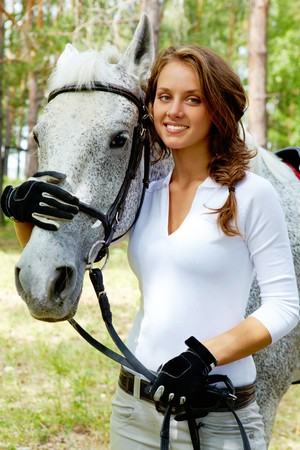 Image of happy female looking at camera with horse near by photo