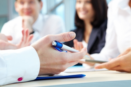business consulting: Image of human hand with pen during seminar or conference
