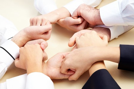 altogether: Image of business people hands holding other symbolizing support and power