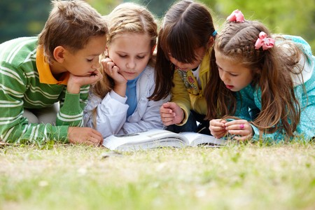 kid reading: Portrait of cute kids reading book in natural environment together Stock Photo