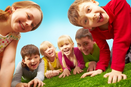 child portrait: Image of happy boys and girls lying on a green grass
