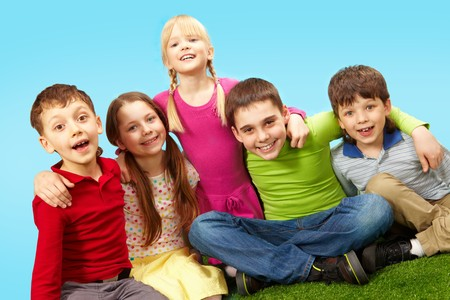 kids hugging: Image of happy boys and girls having rest on green grass Stock Photo