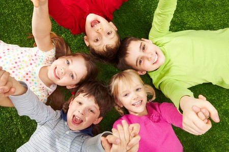 Foto van glimlachen jonge jongens en meisjes liggend op groen gras  Stockfoto