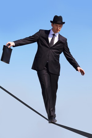 Photo of skilled businessman walking down ribbon or rope with blue sky at background  photo