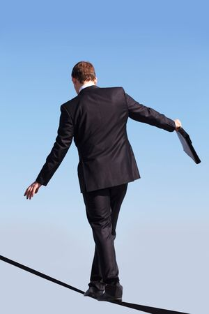 Back view of contemporary businessman walking down ribbon or rope with blue sky at background  photo